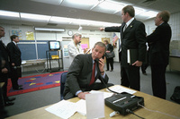 As Deputy Assistant Dan Bartlett points to news footage of the World Trade Center, President George W. Bush gathers information about the attack Tuesday, Sept. 11, 2001, from a classroom at Emma E. Booker Elementary School in Sarasota, Florida.