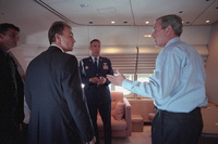 President George W. Bush is briefed by staff about the on going terrorist attack aboard Air Force One after departing Sarasota, Florida Tuesday, Sept. 11, 2001.