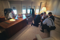 President George W. Bush talks on the telephone Tuesday, Sept. 11, 2001, as senior staff huddle aboard Air Force One.
