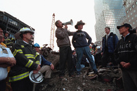 Standing on top of a crumpled fire truck with retired New York City firefighter Bob Beckwith, President George W. Bush rallies firefighters and rescue workers Friday, Sept. 14, 2001,