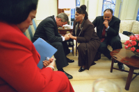 President George W. Bush joins in prayer with Coretta Scott King, left, Bernice King and Martin Luther King III during their visit to the Oval Office. Jan 21, 2002.